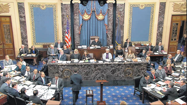 In this image from video, a Senate page brings a question from a Senator to the desk to be read by presiding officer Chief Justice of the United States John Roberts during the impeachment trial against President Donald Trump in the Senate at the U.S. Capitol in Washington, Thursday, Jan. 30 2020.