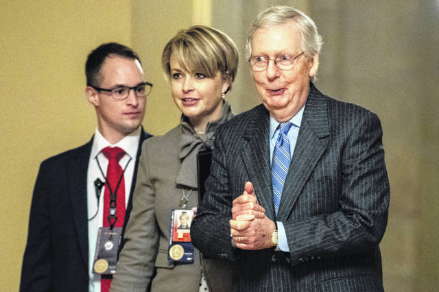 Senate Majority Leader Mitch McConnell of Ky., right, walks to meet with Senate Republicans on Capitol Hill in Washington, Friday, Jan. 31, 2020, after the Senate voted to not allow witnesses in the impeachment trial of President Donald Trump on charges of abuse of power and obstruction of Congress.