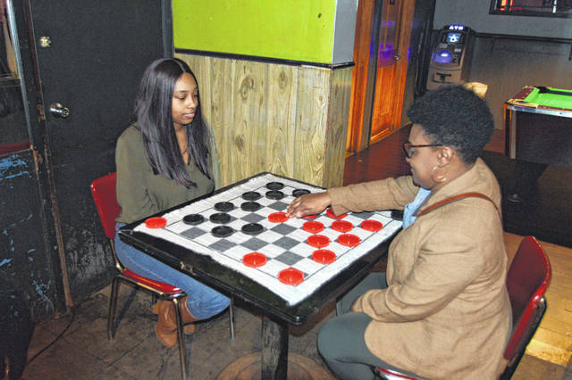 Jamesha Williamson, left, watches Sharetta Smith as she makes her move on a giant checker board.