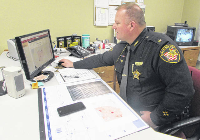 Brian Siefker, Putnam County sheriff, sits at his desk Friday afternoon looking at a report that shows Putnam County had zero traffic fatalities in 2019.