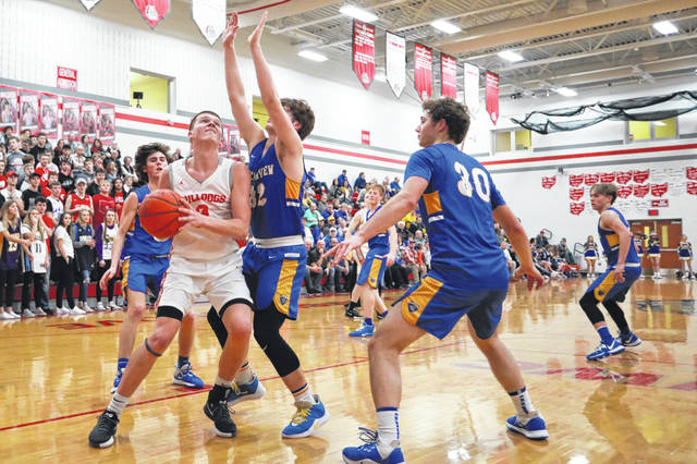 Columbus Grove's Blake Reynolds gets ready to put up a shot against Lincolnview's Creed Jesse (32) and Jake Bowersock (30) during Friday night's game at Columbus Grove High School on Friday evening. Amanda Wilson -The Lima News