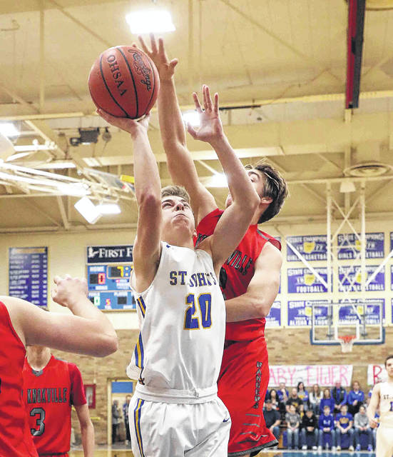 Landon Elwer of Delphos St. John's puts up a shot against New Knoxville's Patrick Covert during Friday night's game in Delphos.
