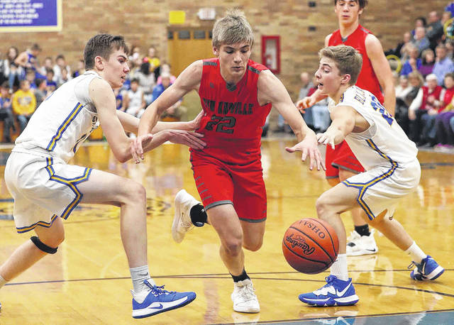New Knoxville's Carson Bierlein drives against Jason Gillespie, left, and Landon Elwer, right, during Friday night's game in Delphos.