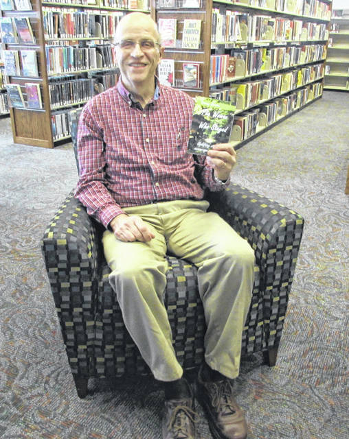 """Ottawa Faith Baptist Church Pastor Denny Coates is pictured with his book """"The Woman Who Stayed"""" that includes stories to encourage and inspire people."""