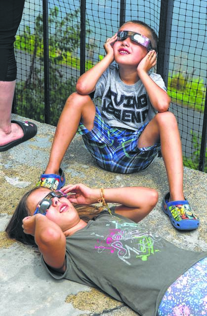 Malachi Onan, 5, and sister Mackenzie, 10, of Lima, used safe viewing glasses to view the partial solar eclipse in 2017 while sitting on the upper deck at Schoonover Observatory. Astronomy buffs say if Lima prepares itself properly, an eclipse coming in 2024 could be very beneficial for the area.