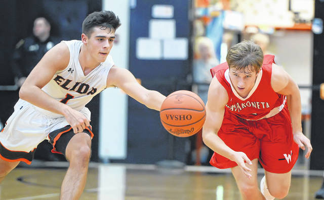 Elida's Dylan Buetner, left, and Wapakoneta's Kaden Siefring compete for a loose ball during Friday night's game at the Elida Fieldhouse.