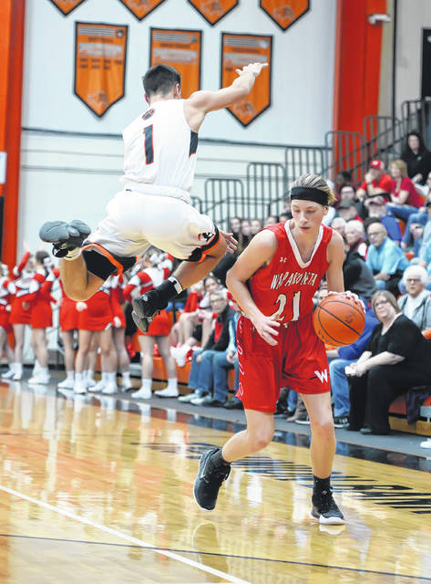 Elida's Dylan Buetner goes airborne while defending Wapakoneta's Trey Ware during Friday night's game at the Elida Fieldhouse.