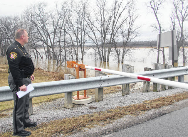 Brian Siefker, Putnam County sheriff, assesses flooding of the Blanchard River by I-9 between Glandorf and state Route 15 that closed the road and many others to be closed.