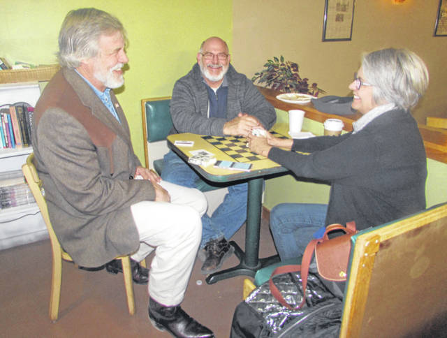 From left are Chris Gibbs, fourth district congressional candidate, at The Meeting Place on Market Friday visiting with Ottawa residents Rick and Erin Hughes.
