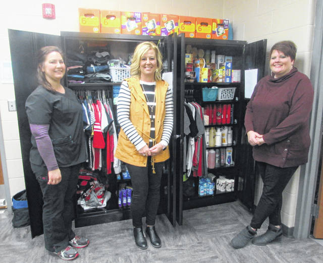 From left are Katie Zimmerly, Columbus Grove schools nurse, Brenda Bruce and Mindy Losh, guidance counselors, standing next to a Caring Closet to provide students with food, hygiene items and clothing.
