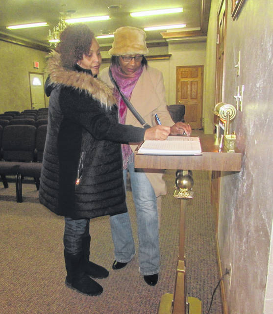 From left are Lima residents Melina Robinson and Michelle Remy signing a memorial register book for the family of Kobe and GiGi Bryant at Jones-Clark Funeral Home Inc. in Lima.