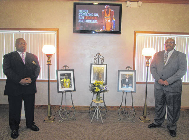 Albert G. Peterson and his brother Mack Peterson Jr., Jones-Clark Funeral Home Inc. employees, stand next to a memorial at the funeral home in memory of Kobe Bryant and his daughter GiGi.