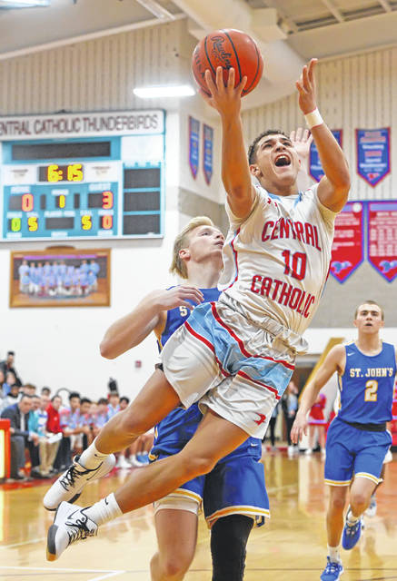 Lima Central Catholic's Rossy Moore goes up for a shot against Delphos St. John's Brady Grothaus during Sunday's game at Msgr. Edward C. Herr Gymnasium.