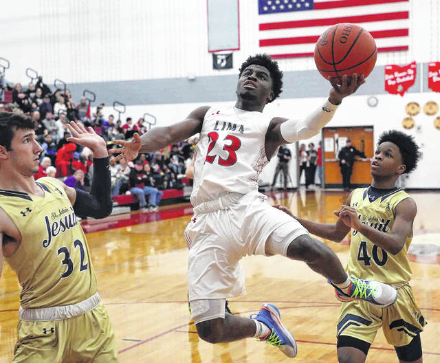 Lima Senior's Jourdyn Rawlins goes up for a shot against Gary Batch (32) and Michael Greenlee of Toledo St. John's during Friday night's game at Lima Senior.