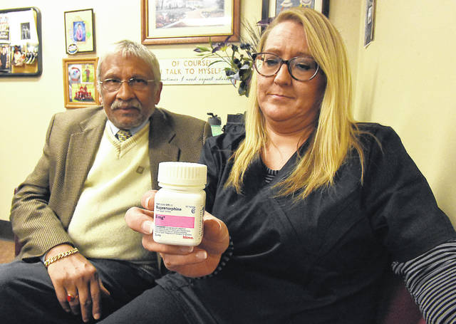 Licensed practical nurse Shelley Hamel, left, holds a bottle of Buprenorphine used in the medication-assisted treatment for pregnant women addicted to opiates, while sitting with Dr. Subrata Roy.