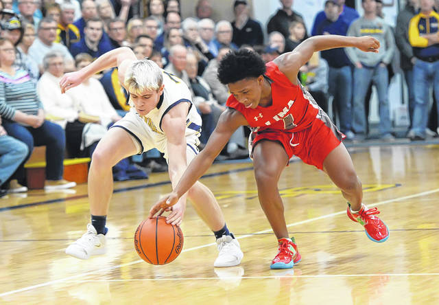 Ottawa-Glandorf's Brennen Blevins, left, and Lima Senior's Khalil Luster compete for a loose ball during Saturday night's game in Ottawa.