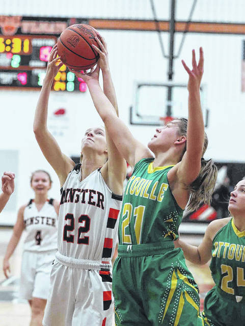 Ottoville's Nicole Knippen (21) and Minster's Mason Pohl battle for a rebound during Saturday's game at Minster.