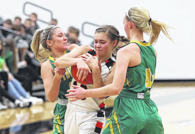 Ottoville Girls Basketball Jocelyn Geise, left, and Alexa Honigford, right, apply pressure against Minster's Janae Hoying during Saturday's game at Minster.