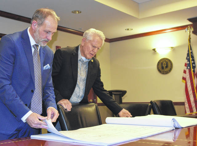 Rhodes State College board of trustees members Douglass Degen and Sam Bassitt look over the architect's drawings for the Center for Health Science Education & Innovation.