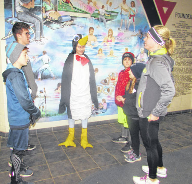 From left, Wyatt and Garret Croy, of Ottawa, and Autumn Knueven, a Putnam County YMCA employee dressed as a penguin, and Everett, Kayt and their mother Cari Croy visit prior to the Chilly 5K.