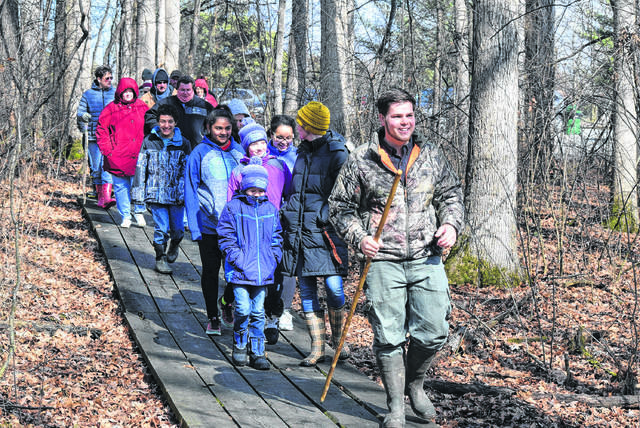Dan Hodges, naturalist with the Johnny Appleseed Metropolitan Park District, leads more than 20 people on a hike through Kendrick Woods in the annual Signs of Spring Nature Hike.