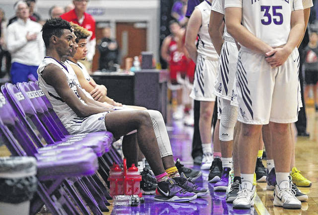 Four Barberton High School basketball players sit on the bench during the playing of the national anthem before the Magics' basketball game Tuesday, Jan. 14, against Northwest. Jeff Lange Photo | Akron Beacon Journal