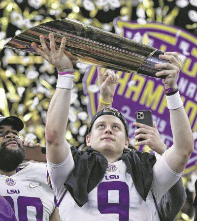 LSU's Joe Burrow holds the national championship trophy Monday in New Orleans.