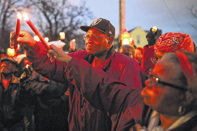 "Leroy and Romaine Jackson, parents of Danielle Lamont ""Bubba"" Jackson who was shot and killed Monday evening, light their candles at a vigil held at 1000 W. North St. on Friday night."