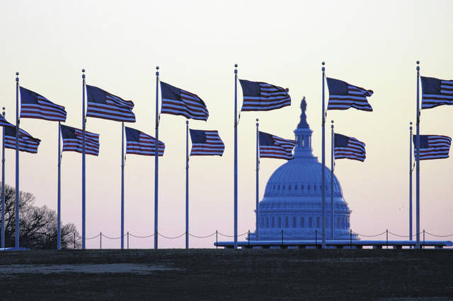 American flags blow in wind around the Washington Monument with the U.S. Capitol in the background at sunrise on Monday. In a four-page resolution, Senate Majority Leader Mitch McConnell said the opening arguments would begin at 1 p.m. on Wednesday, with each side given 24 hours to present their case over a two-day period. The Senate will vote on the resolution Tuesday. (AP Photo)