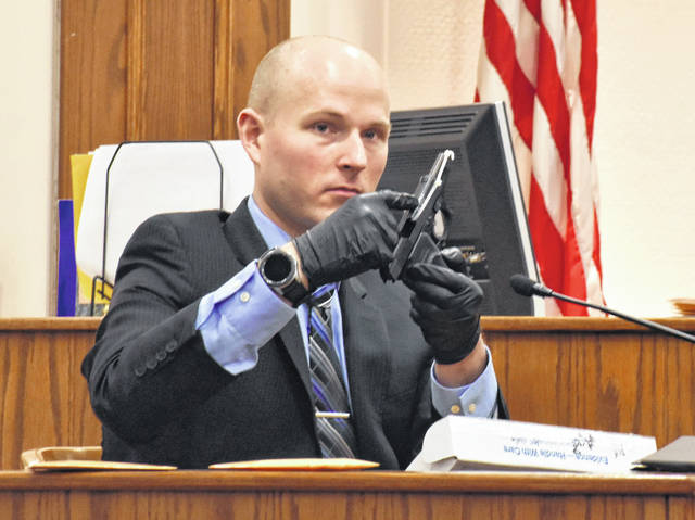 Kevin Belcik, a forensic scientist and firearm examination expert with the Ohio Bureau of Criminal Investigation, shows jurors the semi-automatic handgun he said fired the bullet that was removed from Branson Tucker's body during an autopsy by the Lucas County Coroner's Office.