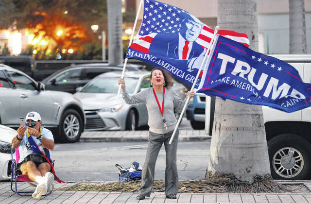 Trump supporters demonstrate across the street from an anti-war demonstration at the Torch of Friendship monument, Thursday, Jan. 9, 2020, in Miami. (AP Photo/Wilfredo Lee)