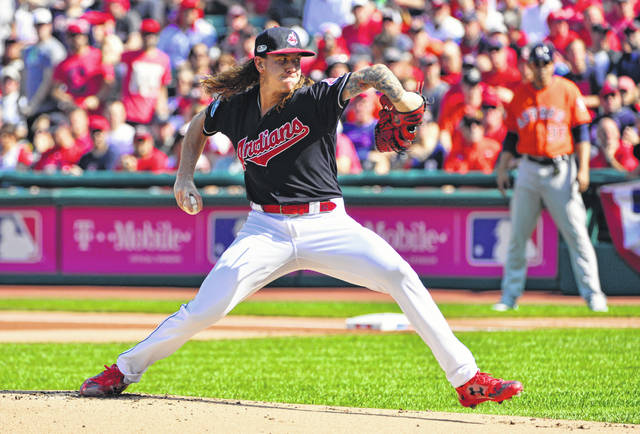 FILE - In this Oct. 8, 2018, file photo, Cleveland Indians starting pitcher Mike Clevinger delivers in the first inning during Game 3 of a baseball American League Division Series against the Houston Astros in Cleveland. Clevinger doesn't know exactly how he''ll react the next time he's on the mound facing the Astros. Clevinger has been one of the most outspoken critics of the Astros since their sign-stealing scandal broke earlier this month, rocking baseball, leading to suspensions, managerial firings in Houston, Boston and New York and blanketing the sport in a net of suspicion as spring training approaches.(AP Photo/Phil Long, File)