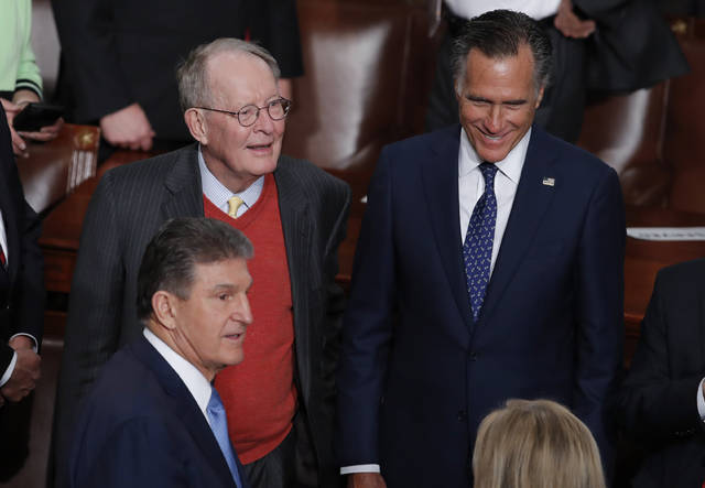 In this Tuesday, Feb. 5, 2020 photo, from left, Sen. Joe Manchin, D-W.Va., Sen. Lamar Alexander, R-Tenn., and Sen. Mitt Romney, R-Utah, arrive for the State of the Union speech by President Donald Trump, at the Capitol in Washington. The Republican-controlled Senate is expected to acquit Trump today in his impeachment trial on impeachment charges of abuse of power and obstruction of Congress. (AP Photo/J. Scott Applewhite)