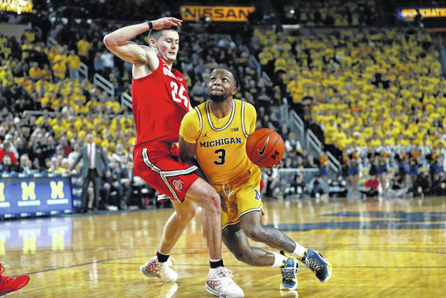 Michigan guard Xavier Simpson (3) drives on Ohio State forward Kyle Young (25) in the second half of an NCAA college basketball game in Ann Arbor, Mich., Tuesday, Feb. 4, 2020. (AP Photo/Paul Sancya)