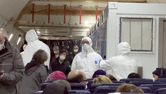 In this image from a video taken on Monday, Feb. 17, 2020, U.S. passengers who evacuated off the quarantined cruise ship the Diamond Princess and officials wait for the takeoff of a Kalitta Air airplane bound for the U.S., at Haneda airport in Tokyo.(Cheryl and Paul Molesky via AP)