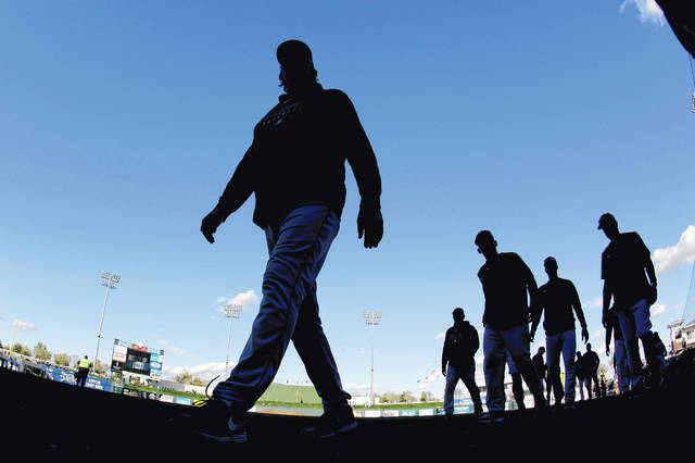 Cleveland Indians players walk to the clubhouse after beating the Kansas City Royals 9-5 in a spring training baseball game Sunday, Feb. 23, 2020, in Surprise, Ariz. (AP Photo/Charlie Riedel)