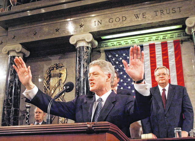 FILE - In this Jan. 19, 1999 file photo, President Clinton acknowledges the crowd prior to giving his State of the Union address on Capitol Hill . House Speaker Dennis Hastert of Illinois is at right. Two decades ago, President Bill Clinton delivered his State of the Union address before a nation transfixed by his impeachment. He didn't use the I-word once. President Donald Trump is far from the first president to deliver a State of the Union address in a time of turmoil.