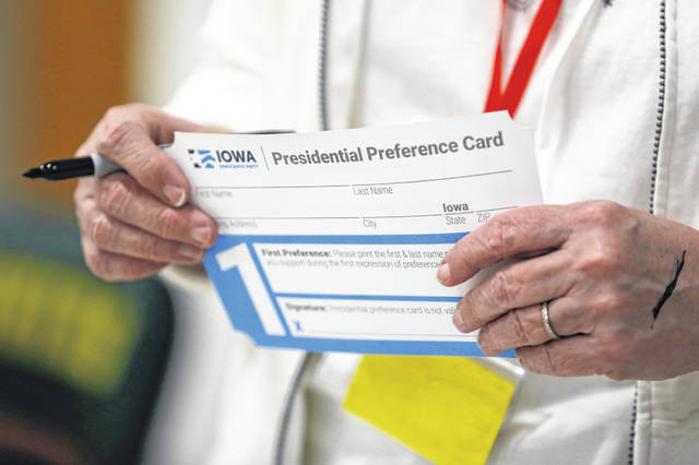A volunteer holds a Presidential Preference Card before the start of a Democratic caucus at Hoover High School on Monday in Des Moines, Iowa.