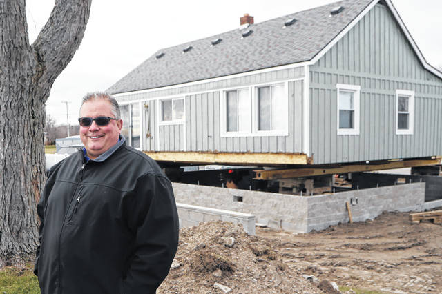 In this Wednesday, Jan. 8, 2020, photo, homeowner Jim Bozynski stands outside his house that is being lifted in Luna Pier, Mich. The project will protect the home from the potential rising lake levels of Lake Erie. High water is wreaking havoc across the Great Lakes, which are bursting at the seams less than a decade after bottoming out. The sharp turnabout is fueled by the region's wettest period in more than a century that scientists say is likely connected to the warming climate.