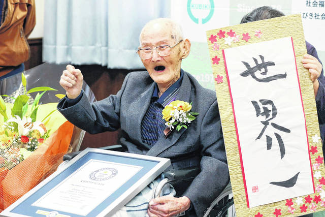 FILE - In this Feb. 12, 2020, file photo, Chitetsu Watanabe, 112, poses next to the calligraphy he wrote after being awarded as the world's oldest living male by Guinness World Records, in Joetsu, Niigata prefecture, northern Japan. The Japanese man who received his certificate as the world's oldest man with a raised fist and big smiles earlier this month has died at 112. Guinness World Records confirmed Tuesday, Feb. 25, 2020 he had died Sunday.
