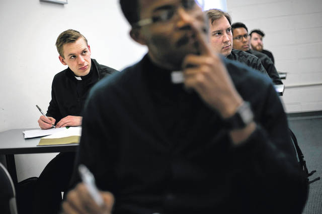 Seminarian Daniel Rice, left, sits with classmates during a lesson on the Gospel of Luke at St. Charles Borromeo Seminary in Wynnewood, Pa., on Wednesday, Feb. 5, 2020. Future Catholic priests remain unflinchingly optimistic despite scandals that have driven faithful from the pews.