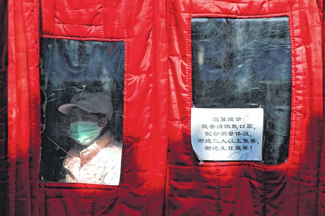 "A worker wearing a protective face mask looks out from a restaurant displaying a COVIC-19 virus precaution notice near Qianmen Street, a popular tourist spot, in Beijing, Sunday, Feb. 16, 2020. China reported Sunday a drop in new virus cases for the third straight day, as it became apparent that the country's leadership was aware of the potential gravity of the situation well before the alarm was sounded. The notice reads: ""Please wear a mask when dining, cooperate to receive temperature check, reject more than three person dining and birthday gathering."""