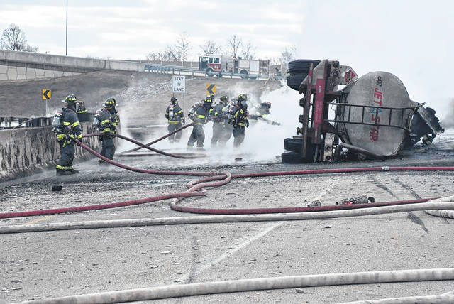 This photo provided by Indianapolis Fire Department shows firefighters trying to put a tanker fire on Thursday, Feb. 20, 2020 in Indianapolis.. The driver of the tanker made contact with a portion of the guardrail on the ramp from I465 SB to I70 E. The contact, split the tank and overturned the semi, after which fire broke out.