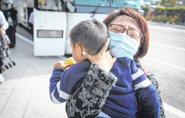 Cynthia, who did not give her last name, traveled from Texas to San Diego to meet her son Alan, 2. He was one of the coronavirus evacuees from China who completed the 14-day quarantine at Marine Corps Air Station Miramar and was released on Thursday. Cynthia was emotional as she holds the toddler, the first one off a charter bus when it arrived at San Diego International Airport from the Marine Corps base.
