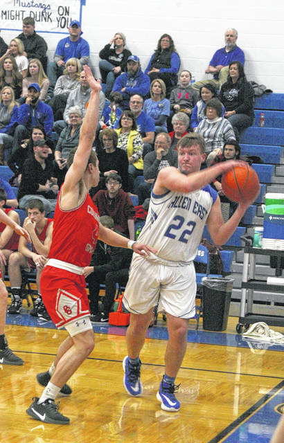 Allen East's Cole Fletcher tries to find the open man as Columbus Grove's Evan Hopkins cuts him off at the baseline during Friday night's game at Allen East.