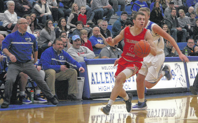 Columbus Grove's Evan Hopkins looks for an open teammate as he races down the court during Friday night's game at at Allen East.