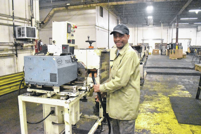 Charles S. Crisp, an employee at BRP Manufacturing Co. in Lima, feeds rubber into an extruder at the Jackson Street plant to produce one of several items made by the company primarily for the defense and automotive industries.
