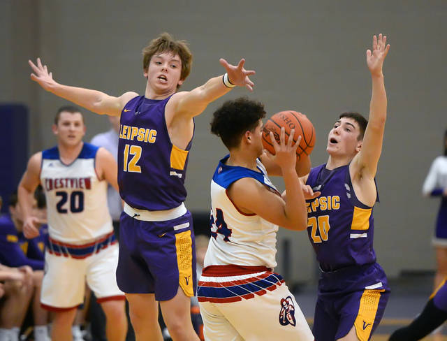 Crestview's JJ Ward looks to pass against Leipsic's Dillan Niese, left, and Drew Liffick during Wednesday's Division IV sectional game at the Sommer Center at Bluffton University.