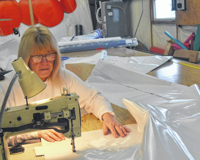 Kim Shively stitches together a seam in one of the workshops at Delphos Tent & Awning, which turns 100 this year.