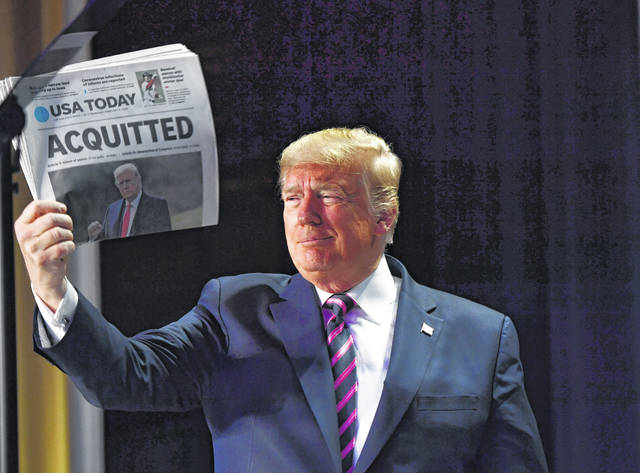 "US President Donald Trump holds up a newspaper that displays a headline ""Aquitted"" as he arrives to speak at the 68th annual National Prayer Breakfast on Thursday in Washington, D.C. Getty Images/Tribune News Service Photo"